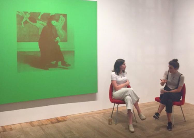 Two women sitting near a large green art work.