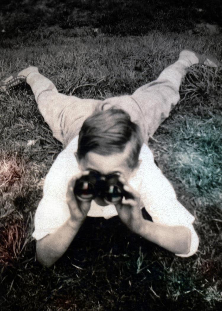Young William Weber holding binoculars