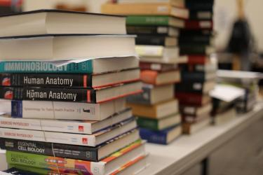 Course reserve books stacked on table.