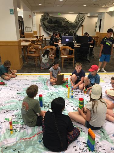 Children sitting on the map.