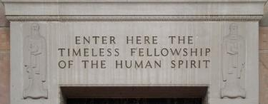 "Stone carving that reads, ""Enter here the timeless fellowship of the human spirit"""