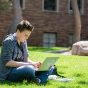 Student sitting in grass with laptop.