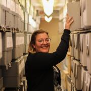 Archivist Ashlyn Velte pulling a box from a shelf in the Archives.