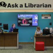 Two librarians at the Ask A Librarian desk