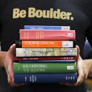 A pile of poetry anthologies held by a CU Boulder student