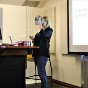 Fellow Julia demonstrates how to use VR goggles during her presentation.