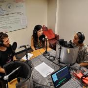 Three students in discussion for podcast.