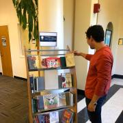 Student looking at shelf of banned books