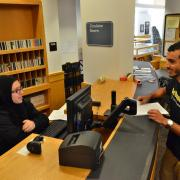 Circulation student assistant assists a patron at the desk of the Earth Sciences Library