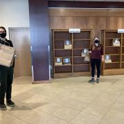 Two people picking up their holds in Norlin Commons