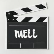 Black and white clapboard with the acronym MELL