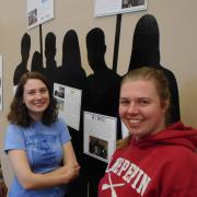 Claire Steffen, in red, with a friend at her exhibit on CU student activism