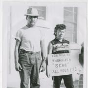 """Man and woman holding a sign that reads, """"You will be known as a scab all your life."""""""