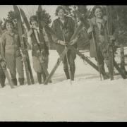 Black and white image of five women with ski gear in the snow, year unknown.