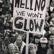 """Protesters with a sign that reads """"Hell No, We Won't Glow"""""""