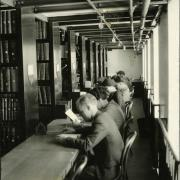 Students sitting at a table studying during finals week from 1933 at Norlin Library