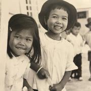 Two young children smiling at the camera, in 1960s Vietnam