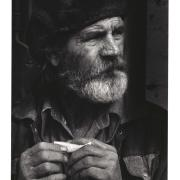 Black and white photo of a man with a beard rolling a cigerette