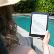 A woman near a pool reading on a tablet