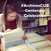 A librarian looks through a box of archival papers
