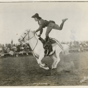 Rodeo performer Bea Kirman on horseback, standing on the saddle with one foot raised, undated