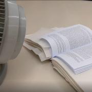 Desk fan drying on book