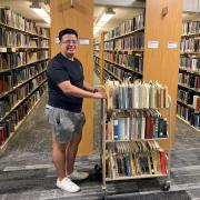 Student smiling with cart of books in the stacks