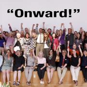 Dean Williams surrounded by former and current faculty and staff with arms raised under the word Onward.