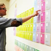 Danny Long, the faculty member who coordinated the exhibit, looks at his students' work.