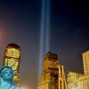 THe statue of liberty in the foreground, twin lights in the background, representing the fallen World Trade Center towers.