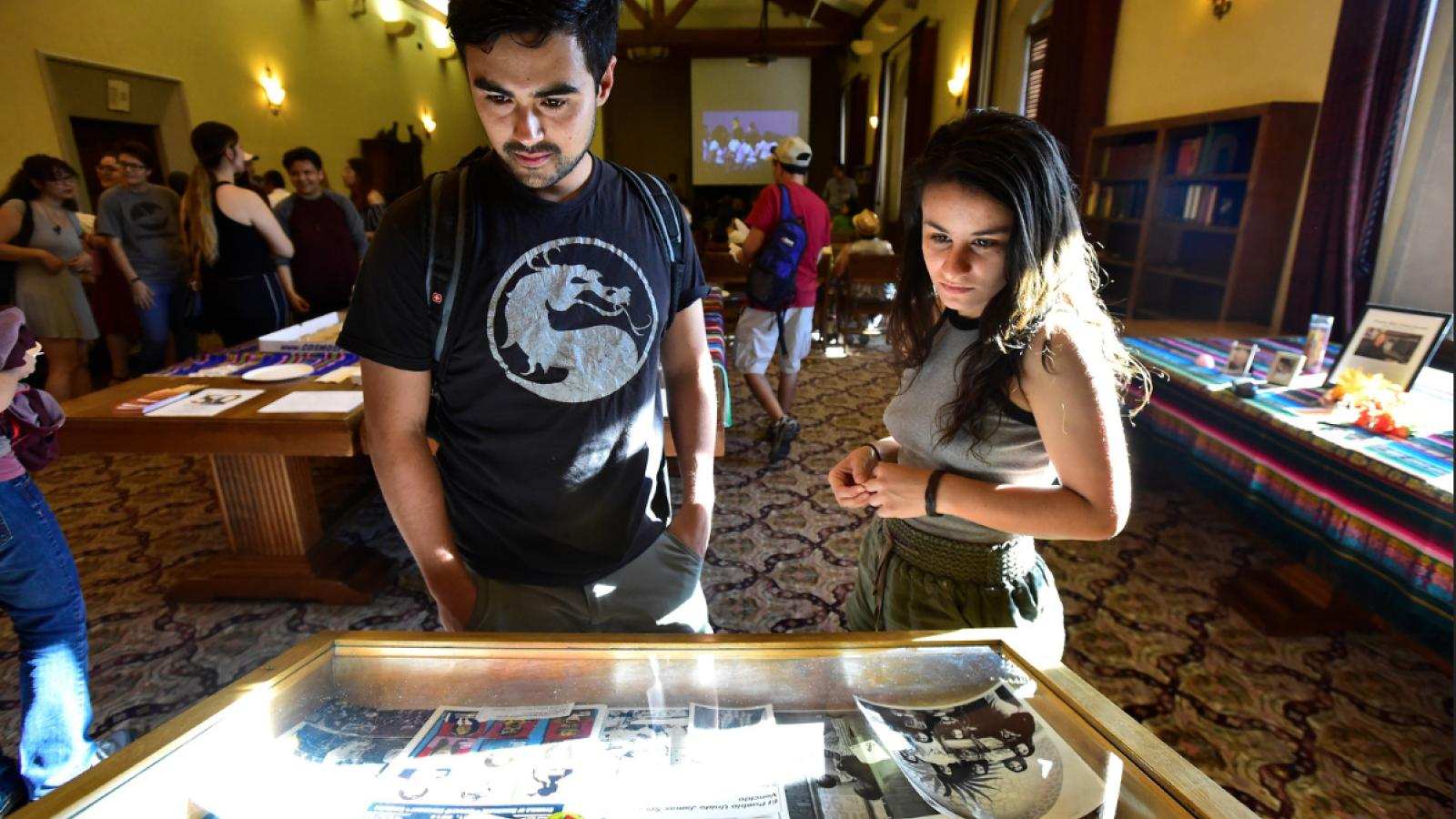 Students looking at an exhibit case at the UMAS celebration.