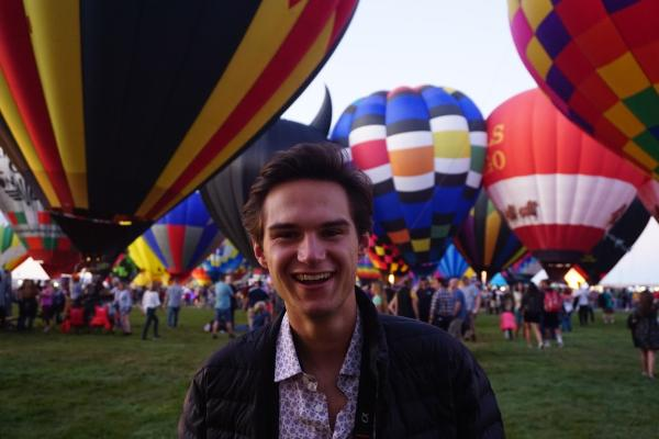 A person smiles at the camera in front of grounded hot air balloons.