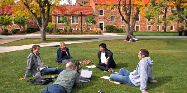 Students sit in a circle in the grass.