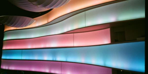 Rows of multi-colored lights fill a dark room.
