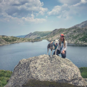 Dr. Rai Farrelly kneels on a large boulder next to a grey and white dog, with a mountain lake in the background and a cloud-strewn sky overhead