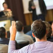 Person with hand raised in a meeting.