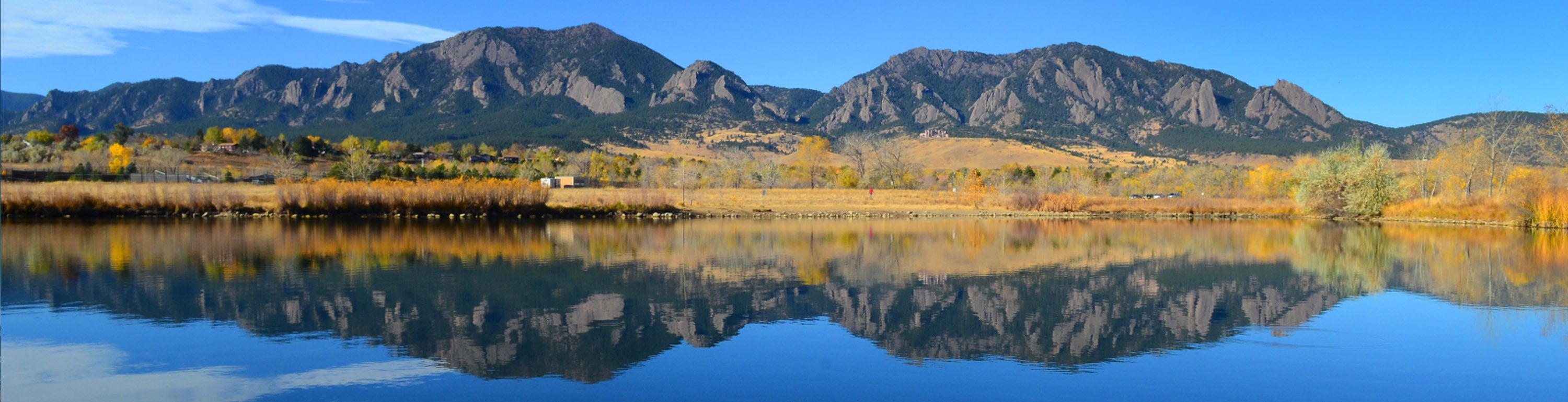 The Flatirons reflecting on a lake.