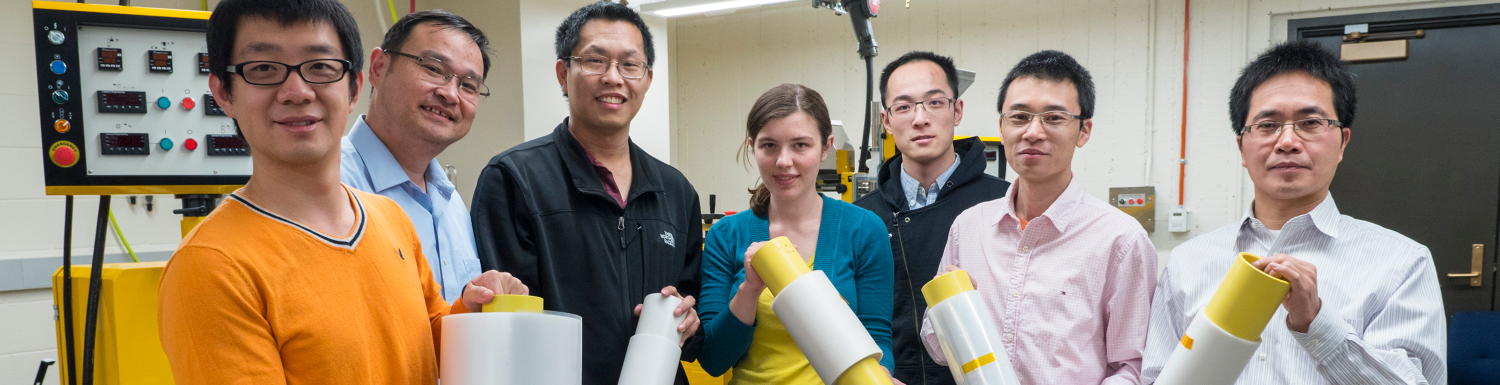 Ronggui Yang and Xiaobo Yin in a lab with a group of students.