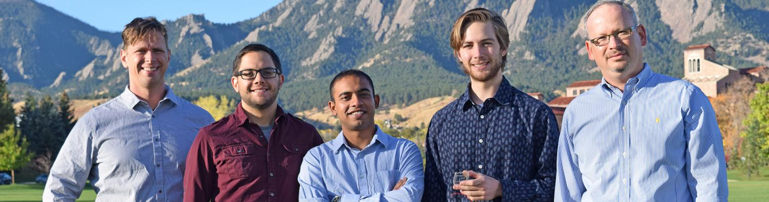 Professor Victor Bright with the research team standing in front of Boulder's Flatiron mountains.