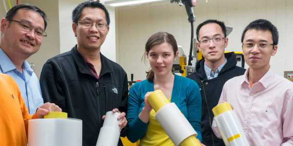 Ronggui Yang and Xiaobo Yin in a lab with a group of students holding rolls of a film material.