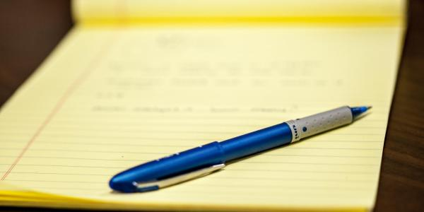 A yellow notepad withn a pen resting on it.