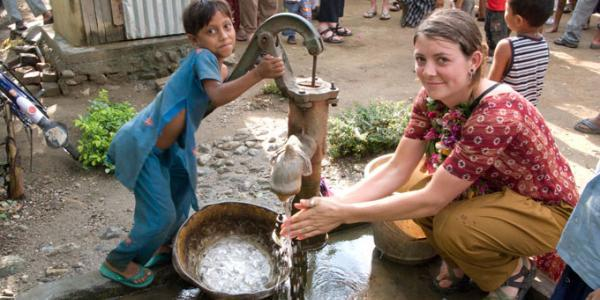 A student with a small child at a hand operated water pump.