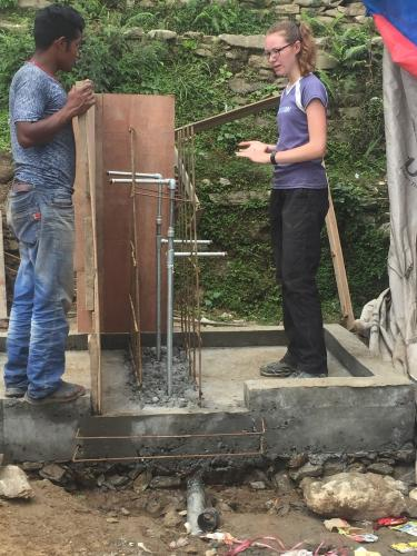 Emily (right) discusses concrete forming for tapstand construction.