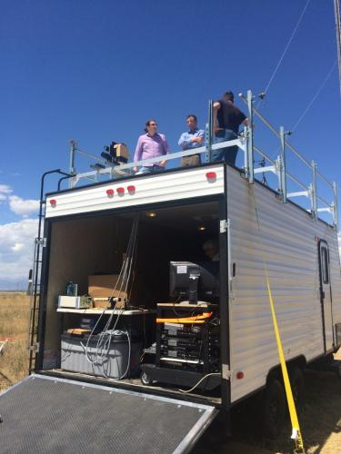 Principal investigator Greg Rieker, center, in blue, discusses discusses the project with team members while atop their mobile laboratory in rural Colorado.
