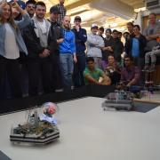 Two robots in the arena with students watching.
