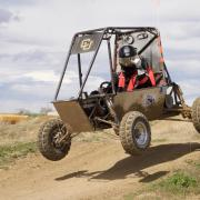 The baja vehicle getting air over a hill.