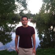 Masoud Aghajani standing by a lake.