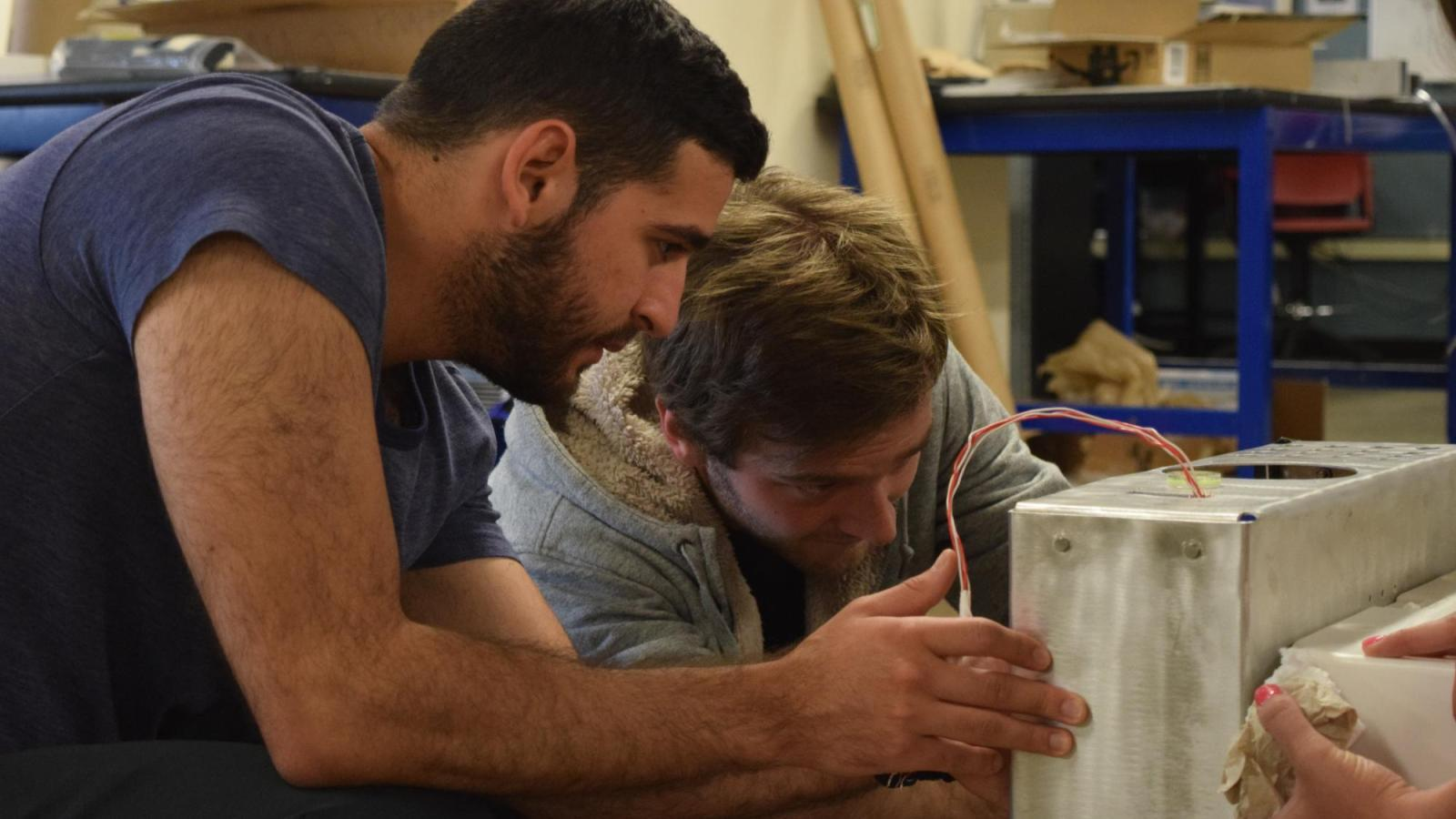 Two students working on a cooler device for long term storage of medical supplies following natural disasters.