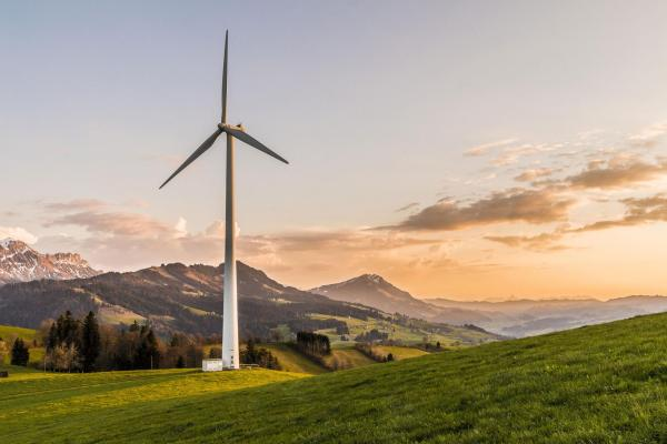 Single wind turbine with mountain backdrop
