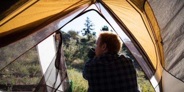 Man sitting in tent and sipping coffee